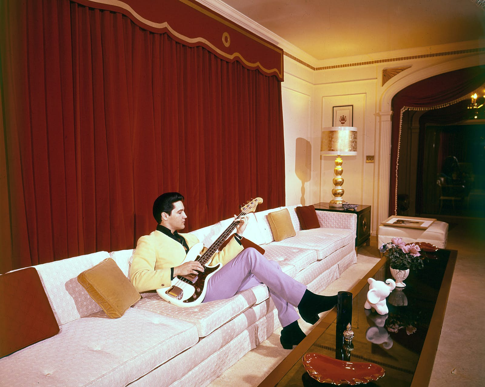 Elvis sitting on a white couch with a bass guitar