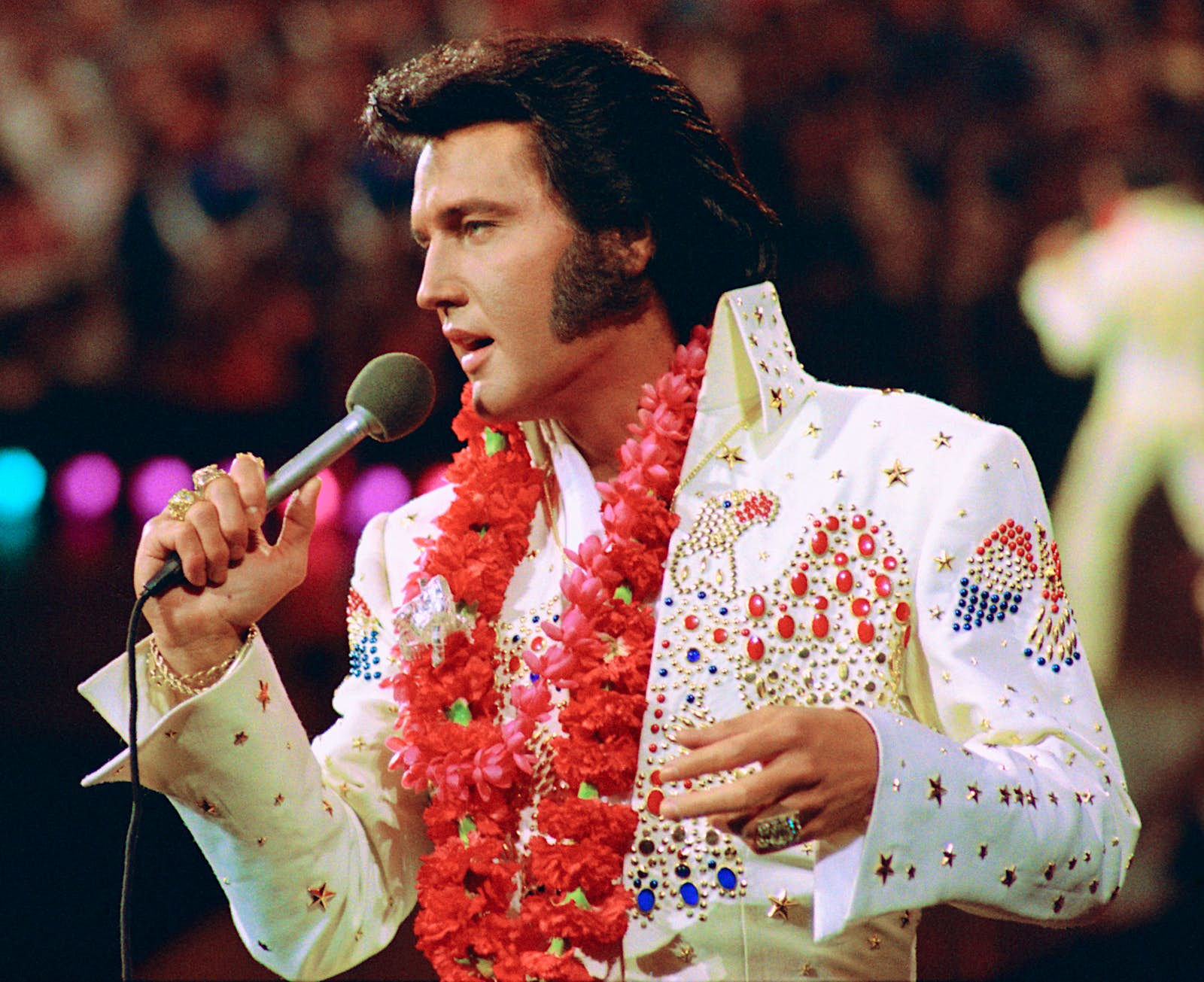 Elvis Presley wearing a lei over a white pants suit decorated with red and blue gems and golden stars. He's holding a microphone