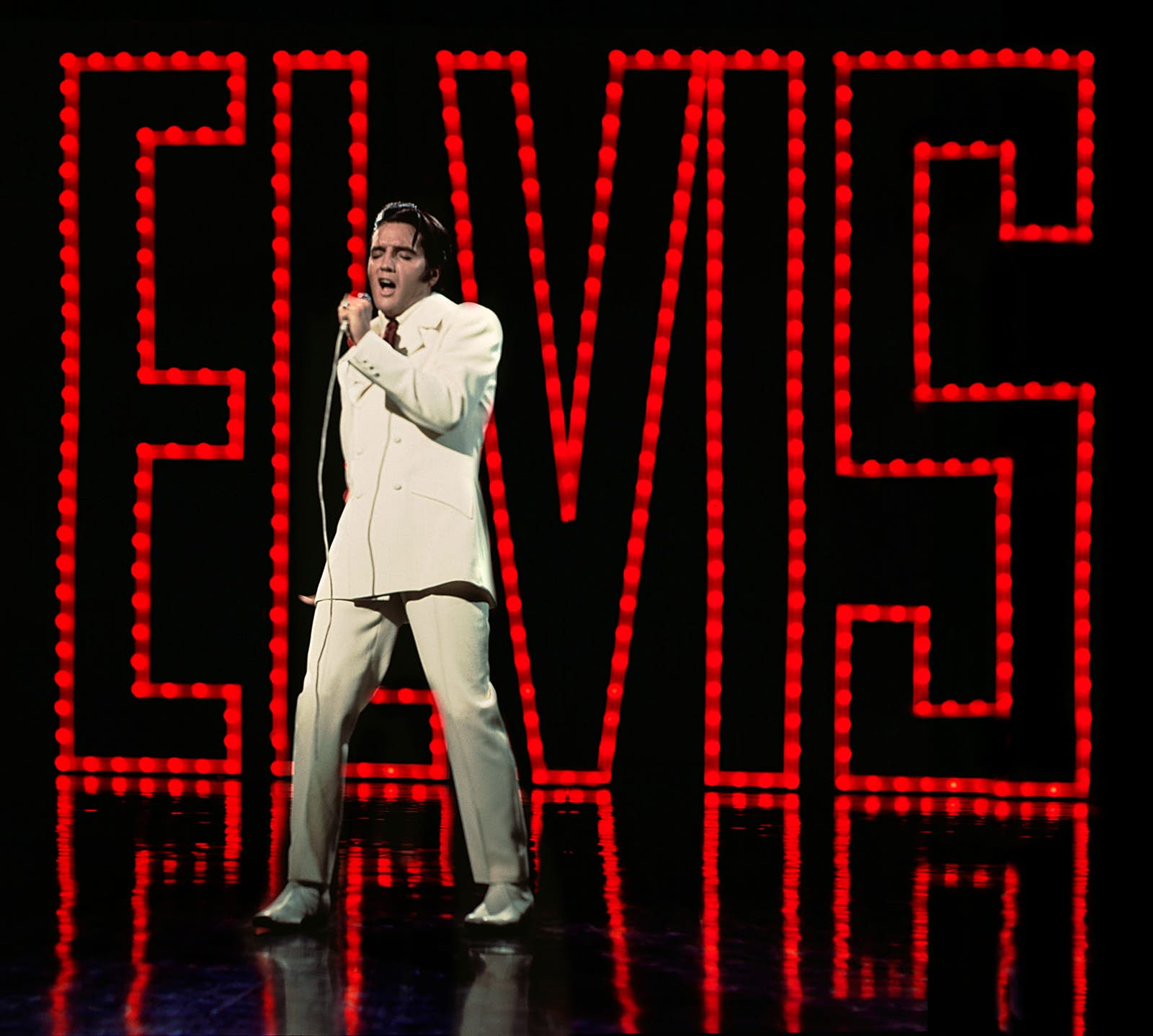 Elvis Presley in a white suit on stage, in front of a series of red lights that spell ELVIS