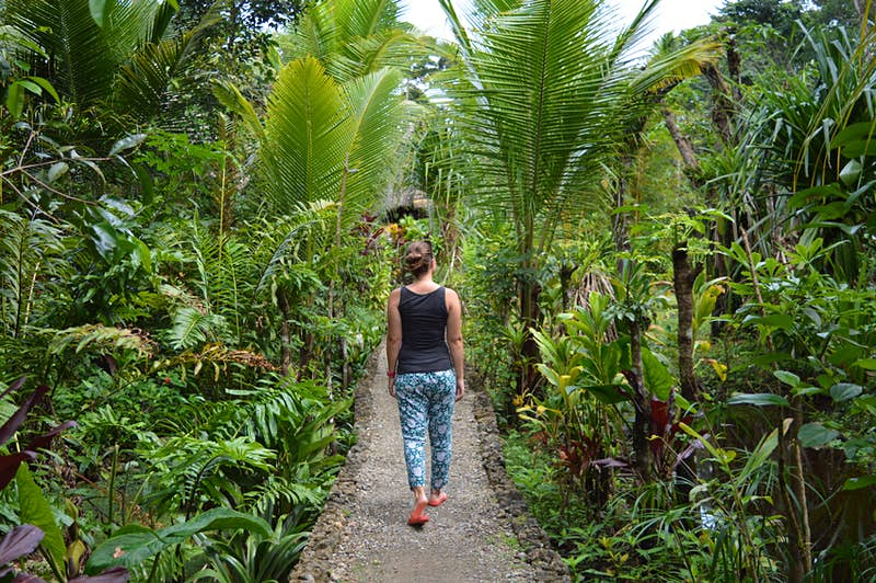 Photo of a woman from behind wearing flip flops, trousers and a tank top as she walks on a dusty path through lush tropical gardens in Guatemala