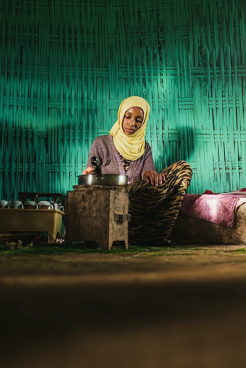 An Ethiopian girl prepares a coffee ceremony; she is wearing a yellow headscarf and sitting in front of a turquoise wall.