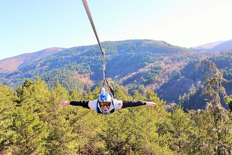 A man on a zip line at Pena Aventura, far above treetops with hills beyond; he is facing the camera with arms outstretched.
