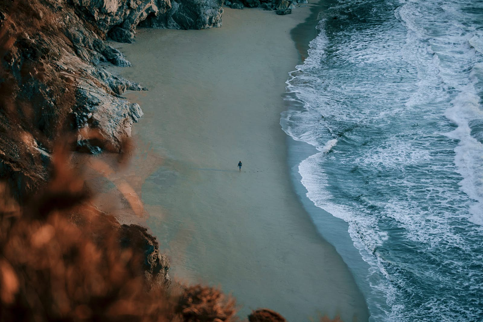 An aerial view of a lone figure walking the beach in Big Sur in California, under a moody light; the sea looks powerful and there are cliffs behind the beach.