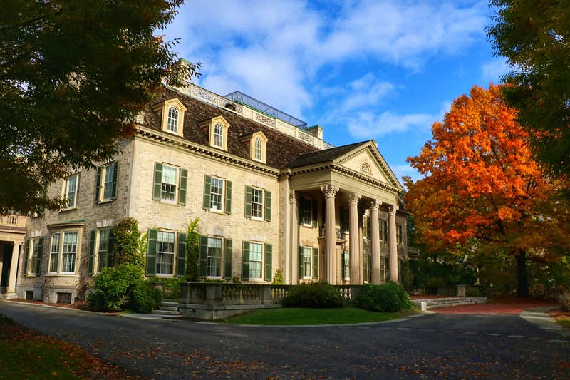 An exterior of the George Eastman Museum, with orange leaves surrounding