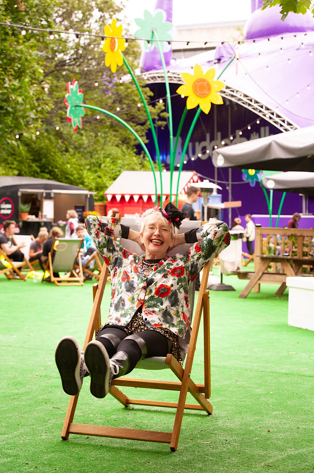English actress and singer Su Pollard poses during a photocall to promote her show 'Harpy' at the Edinburgh Festival Fringe at Underbelly George Square. She is sitting in a deckchair with her hands behind her head and feet raised, there are plastic flowers and the Underbelly venue in the background.