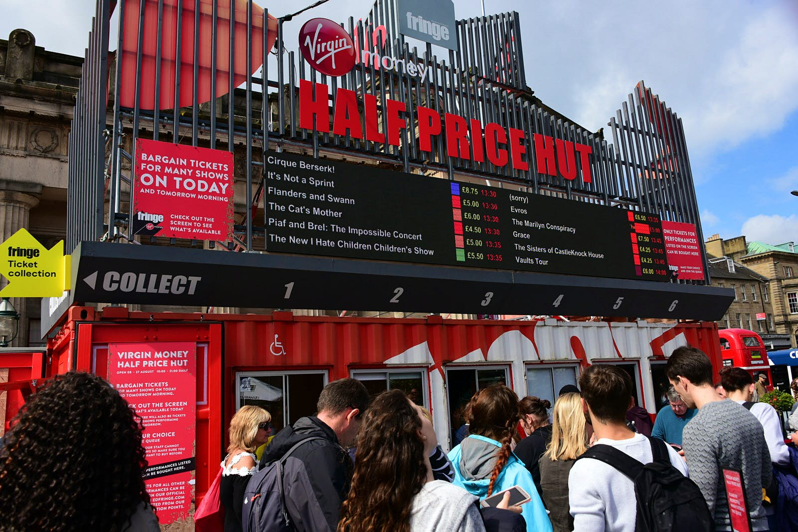 """Festival-goers on The Mound precinct queue outside the """"Half Price Hut"""" ticket office during the Edinburgh Festival Fringe. The office is in a shipping container painted red and white with windows to serve customers through."""