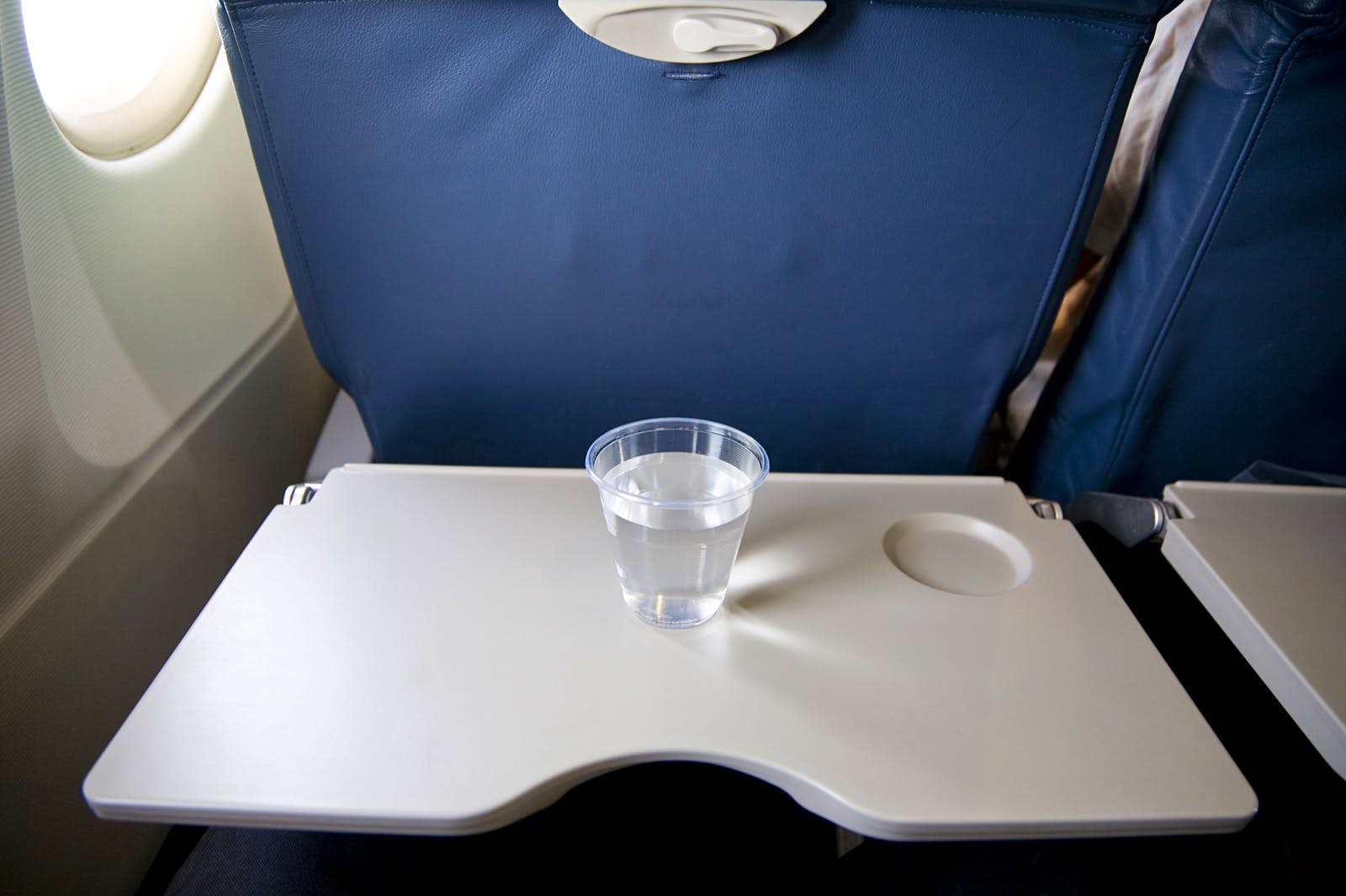 A small cup of water on a tray table inside a plane; tips for a long-haul flight