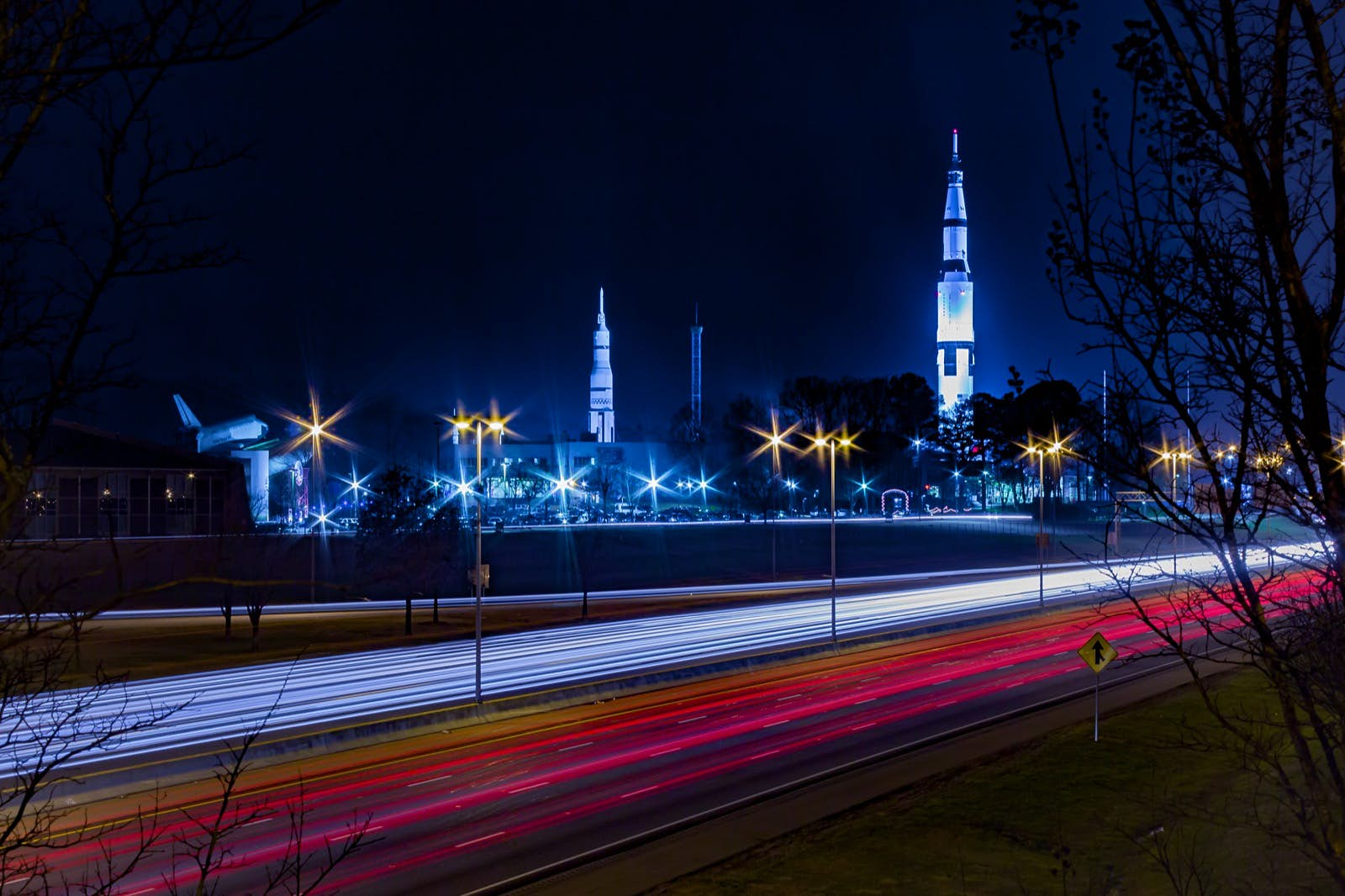 A long exposure shot of US Space and Rocket Center Huntsville, AL with highway traffic. There are parallel streaks of red and white from the car lights in the foreground and the white, needle-like shuttles are visible in the background; Apollo anniversary experiences