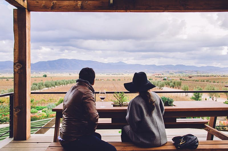 Features - Rear View Of Friends Sitting On Bench In Gazebo Against Landscape