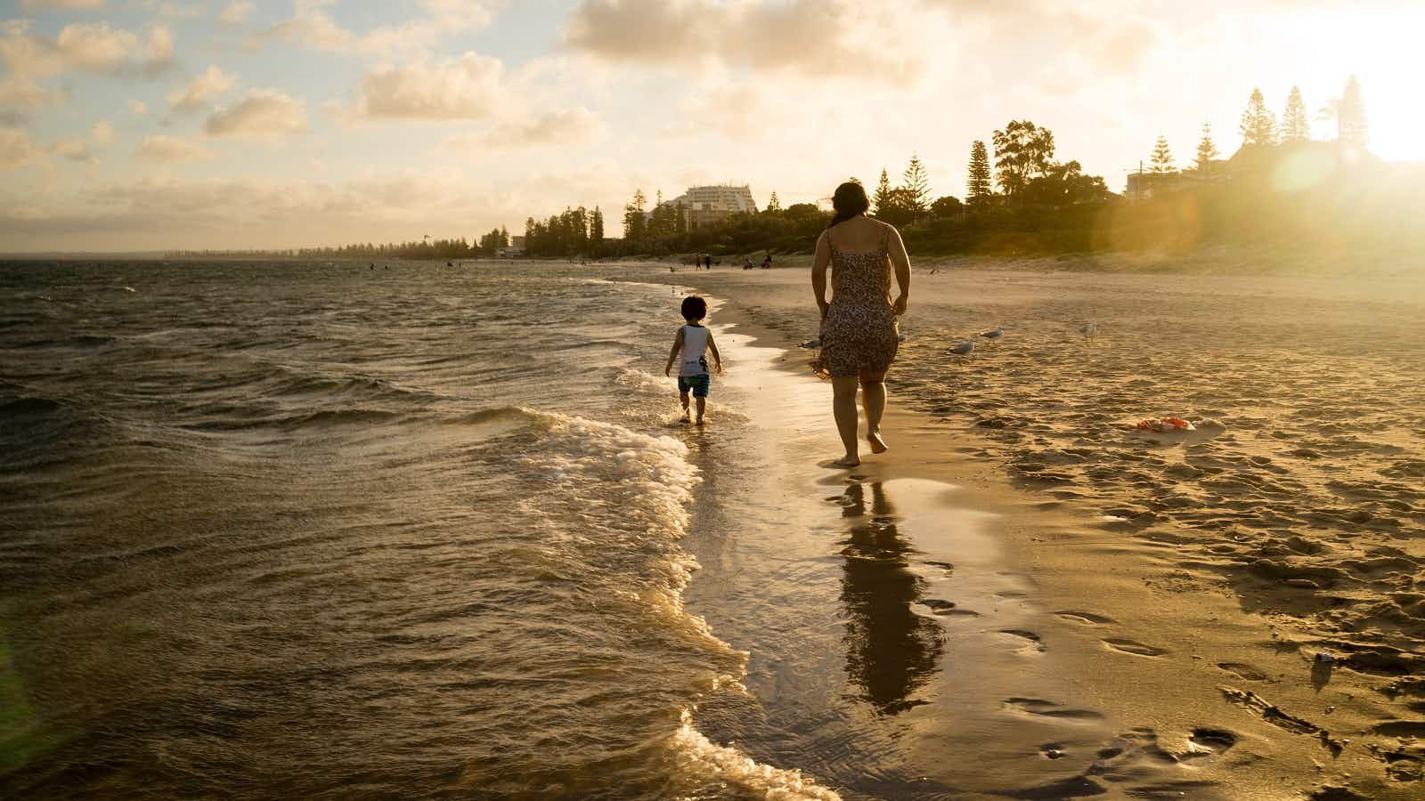 A parent and toddler are silhouetted as they walk on the edge of the sea away from the camera
