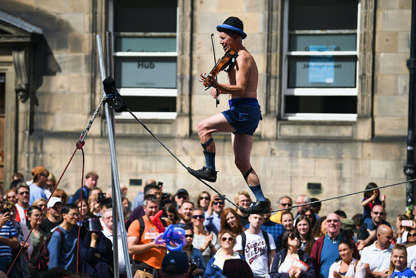 Edinburgh Festival Fringe entertainers perform on the Royal Mile. The Fringe is the largest performing arts festival in the world, with an excess of 30,000 performances of more than 2000 shows. A man is walking along a high line wearing shorts and a bowler hat while playing a violin. A huge crowd is gathered around to watch.