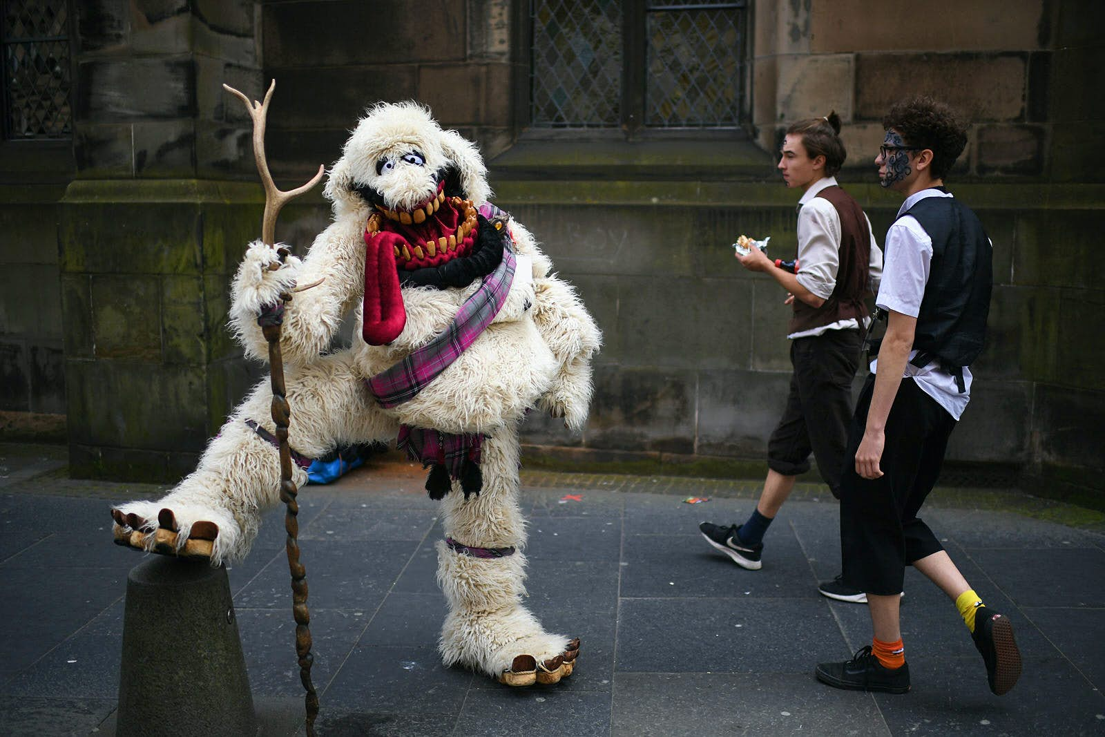 Edinburgh Festival Fringe entertainers perform on the Royal Mile. A person in an oversized white yeti costume with a tartan sash and holding a staff props their leg up on a bollard while two men walk by.
