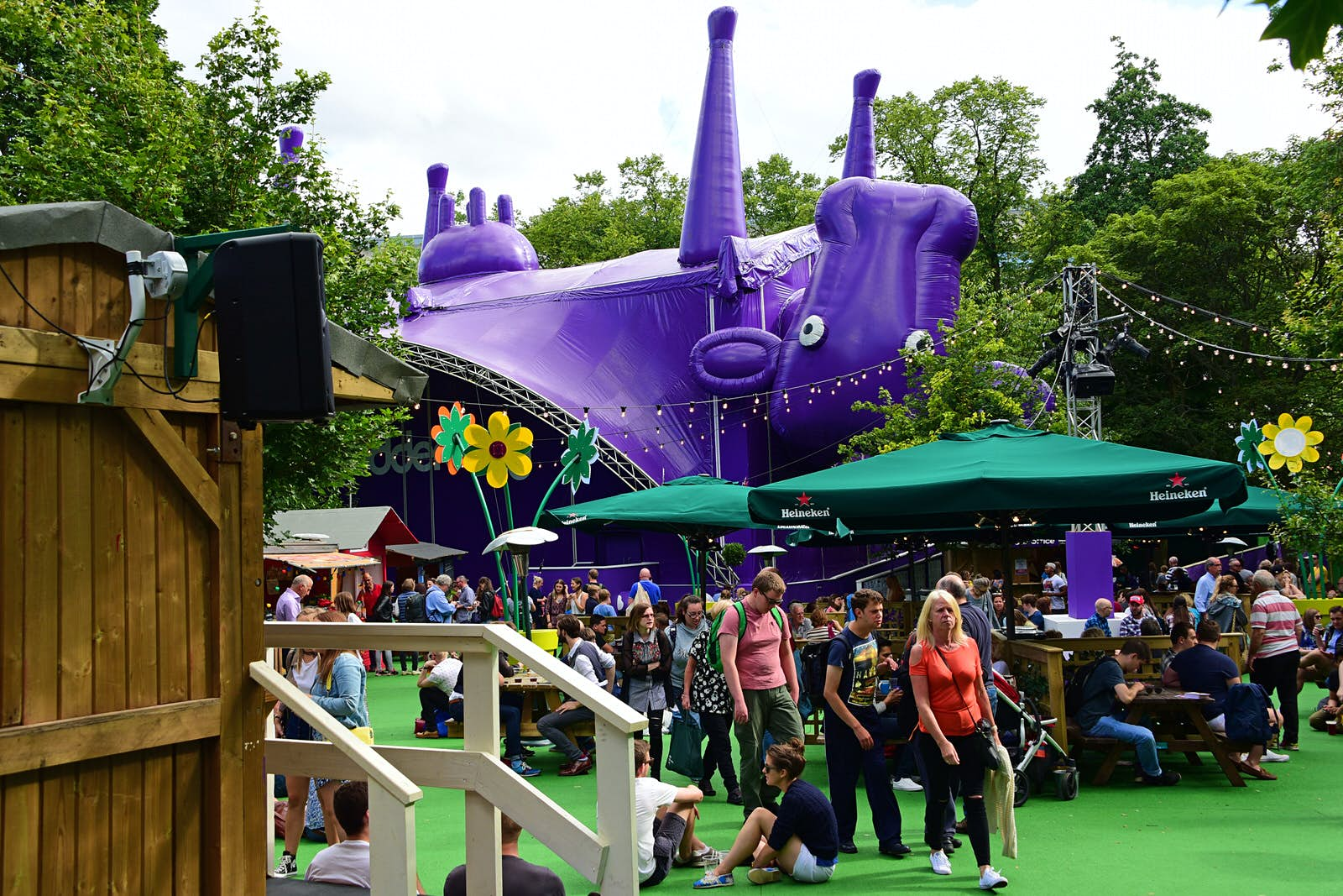 Fringe-goers enjoy the sunshine in the Underbelly Pasture, one of the off-street venues for the Edinburgh Festival Fringe. The Underbelly stage is a hug inflatable upside down purple cow.