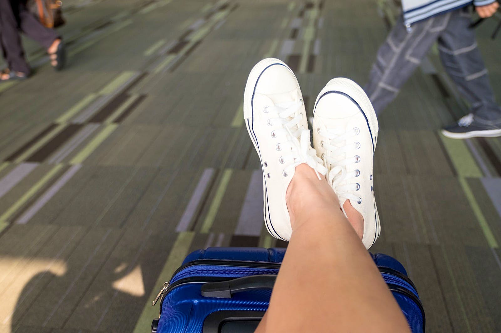 Close up of a person crossing their legs wearing white sneakers propped up on suitcase at an airport terminal; tips for a long-haul flight