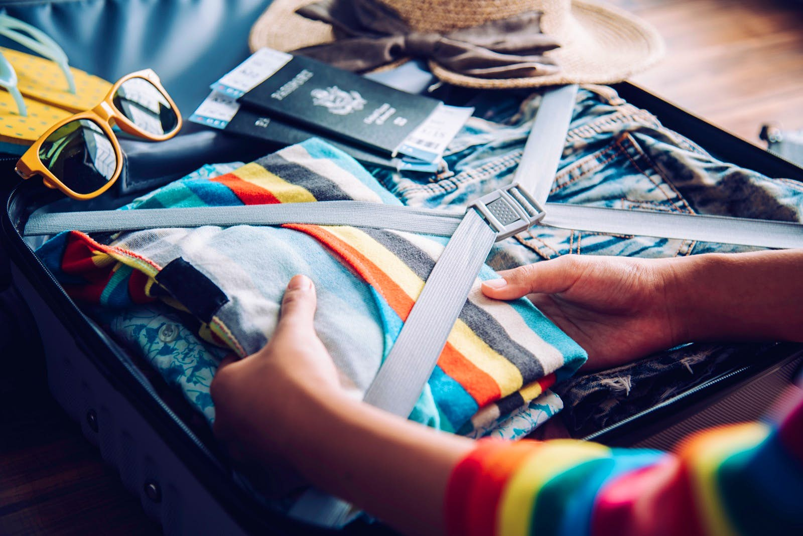 A woman packs a striped, colorful shirt into a suitcase, with sunglasses and a pair of passports nearby; tips for a long-haul flight