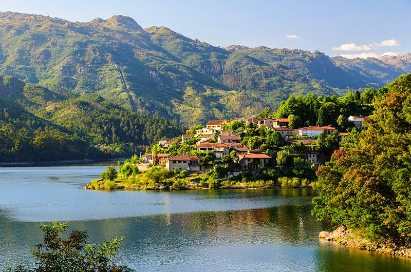 A view of a village clinging to a hill rising from the banks of the Cavado river in Peneda-Gerês national park in northern Portugal, with rugged green hills beyond.