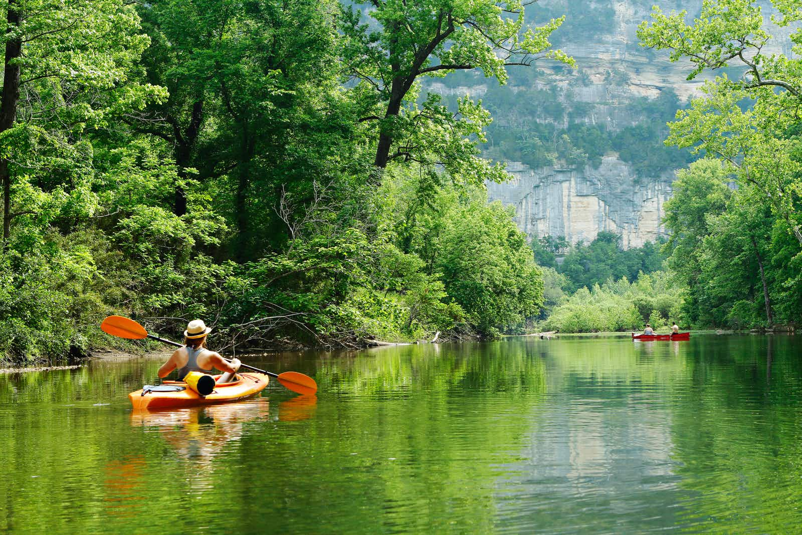 Kayakers on a river surrounded by green trees; summer escapes in the Southern US