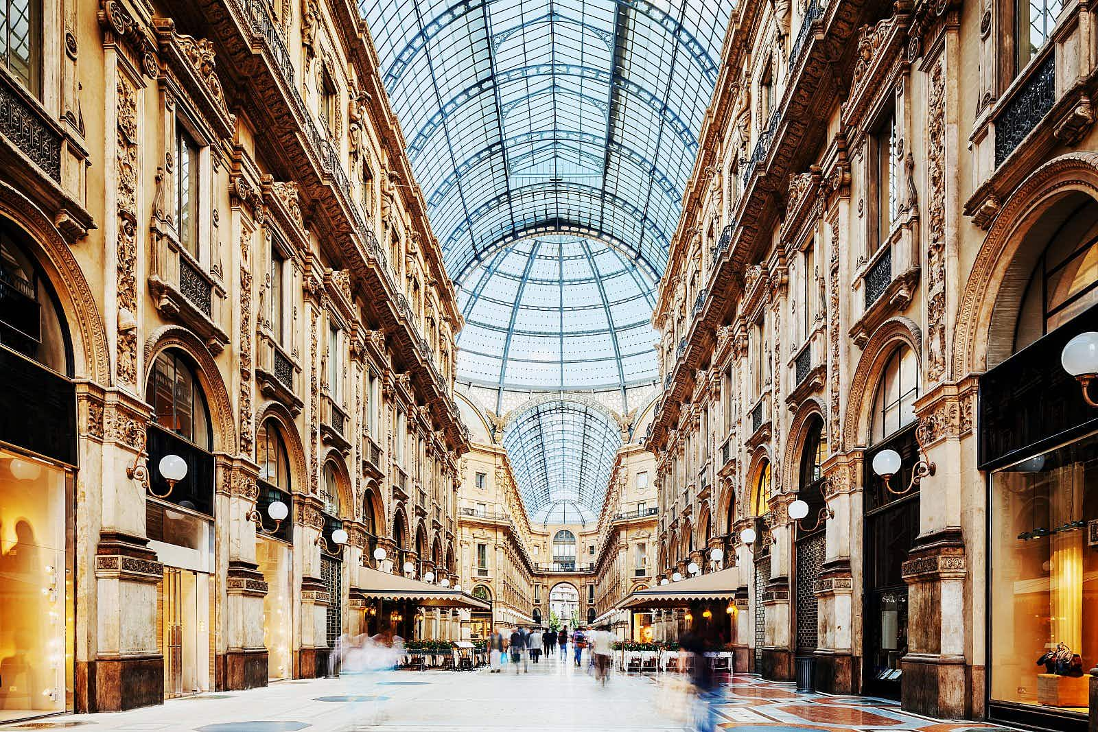 Inside the neoclassical Galleria Vittorio Emanuele II shopping arcade, looking up to its roof made of iron and glass, with upmarket stores either side of the arcade.