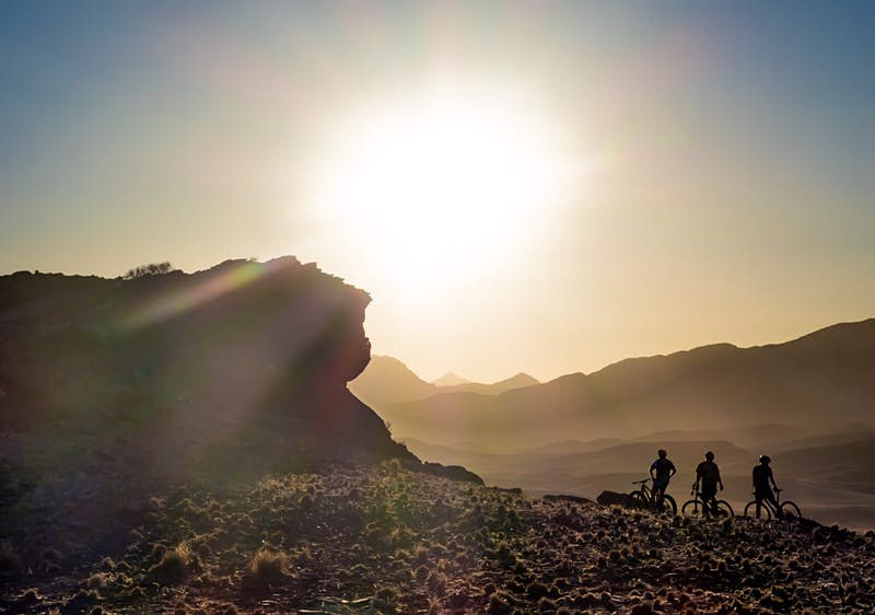The silouette of three people on bicycles next to a large rock in front of a setting sun