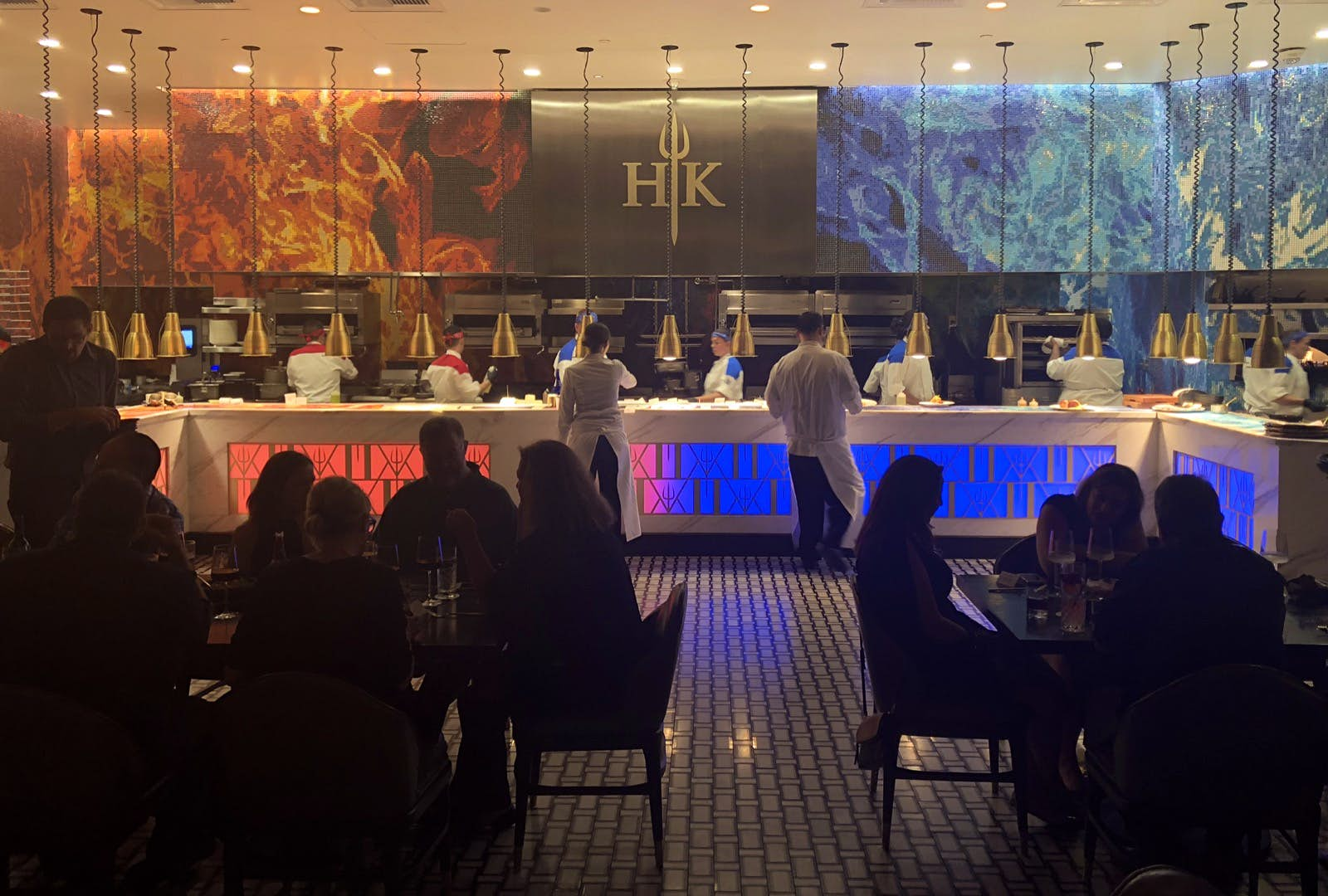 Red and blue flames mark a mural above a long kitchen as diners sit in the dark and waiters move back and forth at a celebrity chef restaurant in Las Vegas