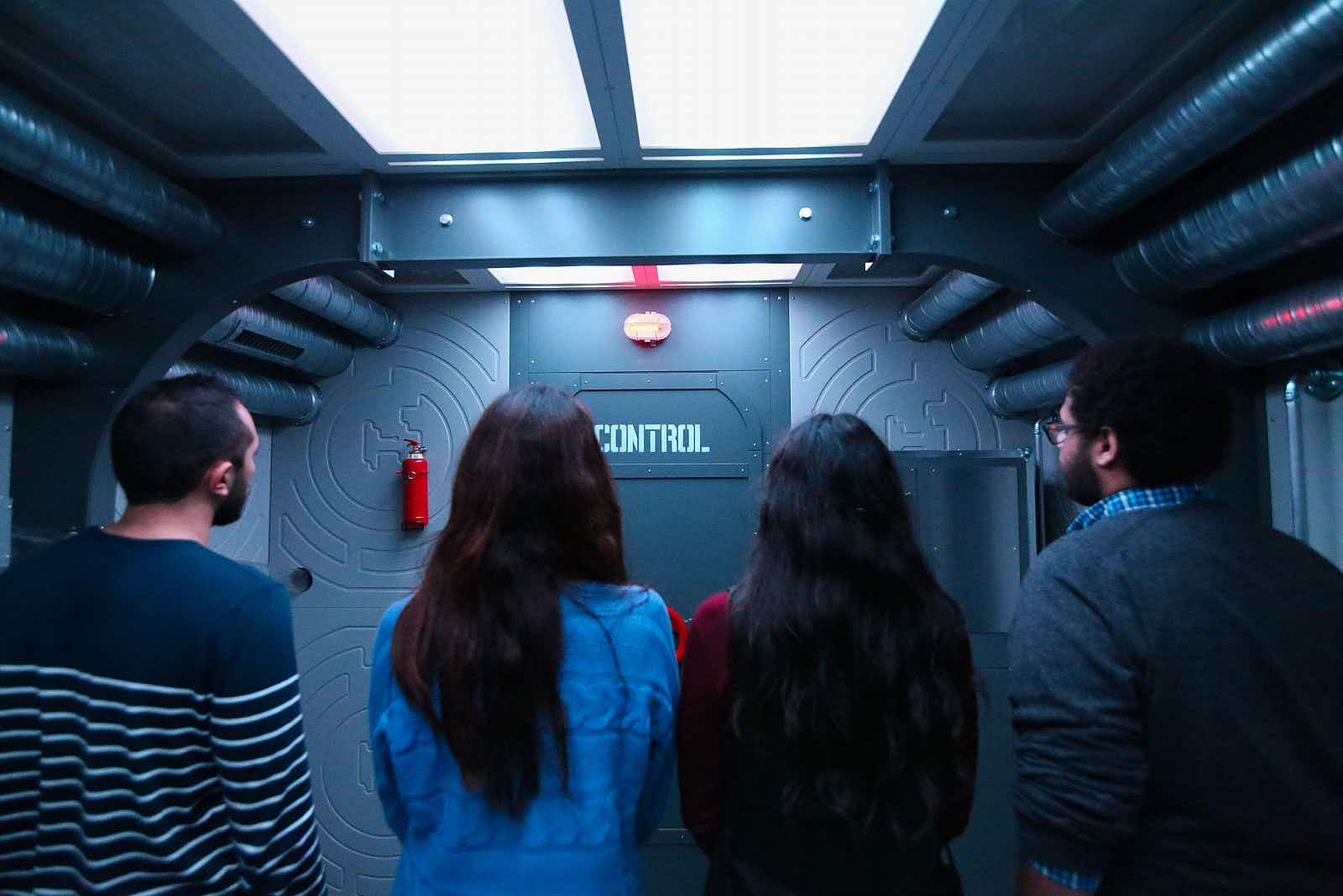 """Four people stand with their backs to the camera facing a door that says """"Control"""" in a grey industrial-looking room; the ceiling is covered with strip lights and silver pipes."""