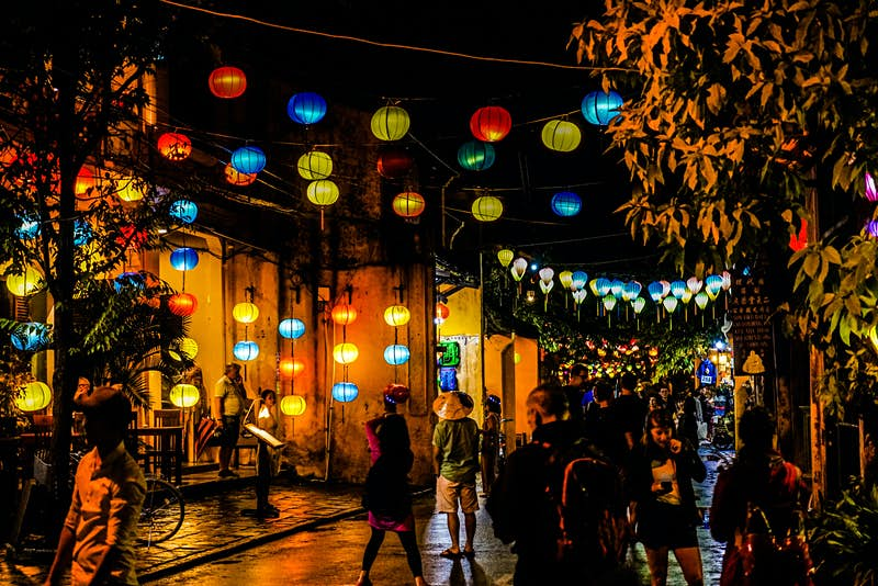 Colourful paper lanterns are strung across the street creating a warm atmosphere in the darkness