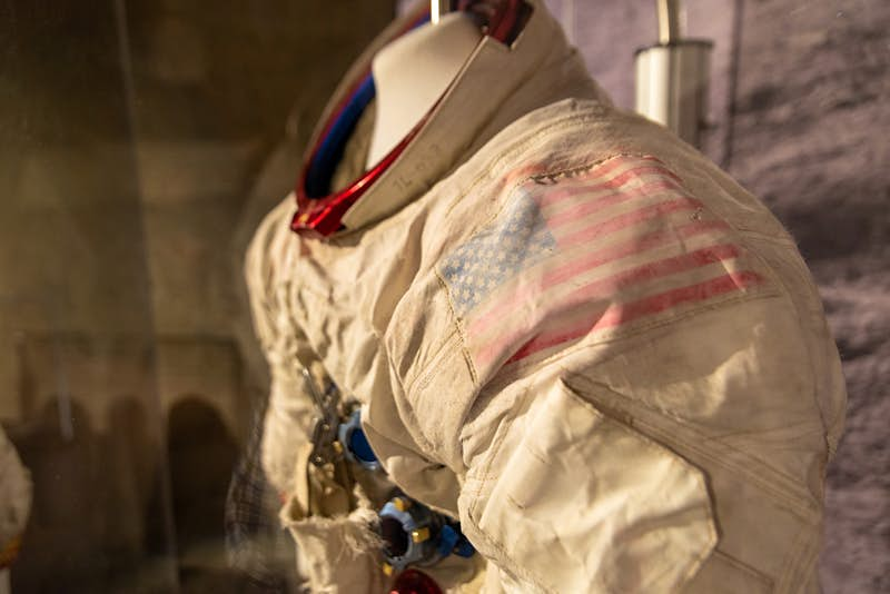 A closeup of an Apollo-era spacesuit, there's a faded American flag emblem on the left shoulder