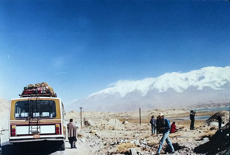 A bus is stopped on a remote road on the left of the picture. People are standing around taking pictures on the rocky ground to the right. Snow capped mountains loom in the back of the photo and the sky is blue and cloudless.