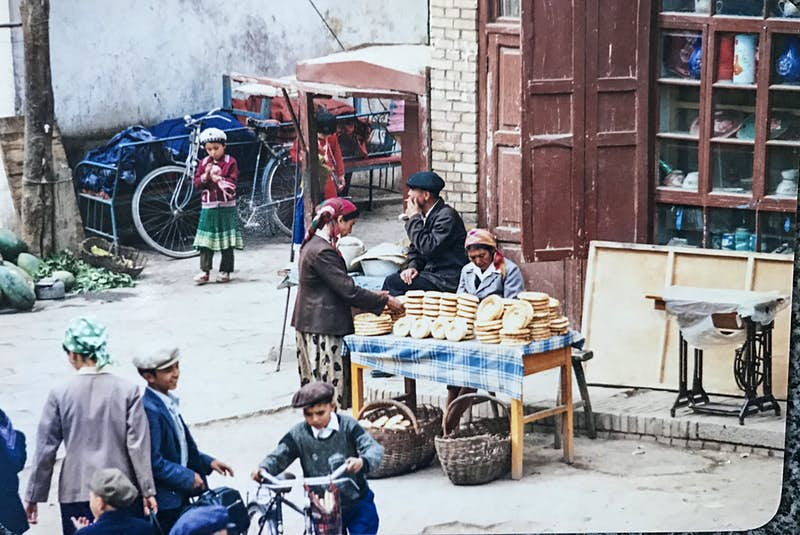 A table is set up on the side of the street and is covered in flat bread. A woman is looking at the bread on display while a child plays in the background and two young boys are on their bikes in the foreground. The stall is set up in front of a building with several windows.