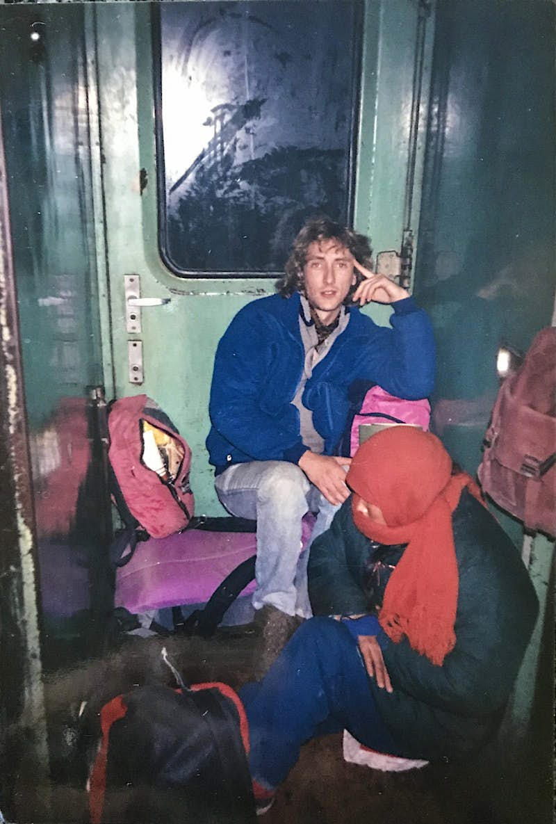 Steve and another person sit in a narrow part of a train by a doorway. They have bags around them and look uncomfortable. Ice is visible on the edge of the door.