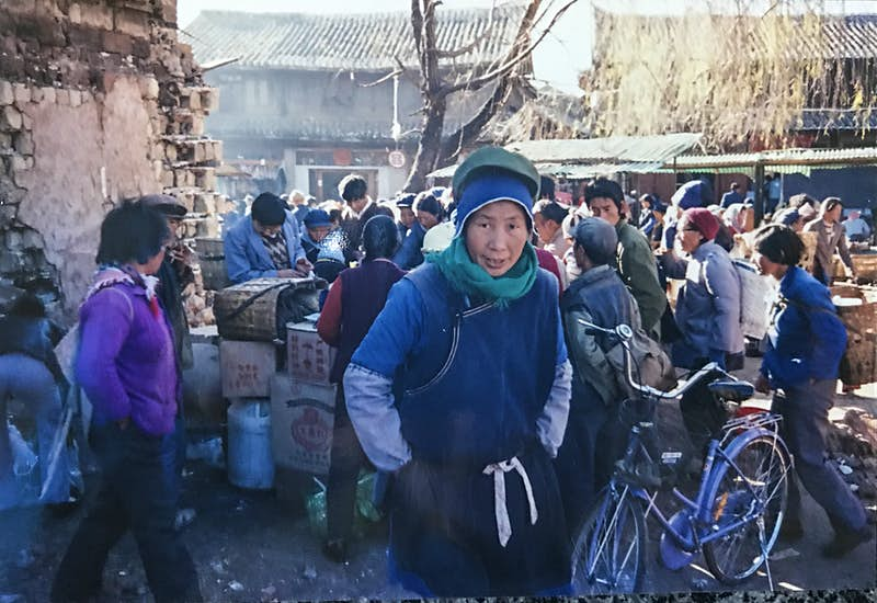 A scene of the heavily crowded market area. A Chinese woman in a blue jumper and hat, and black apron, stands in the foreground staring at the camera.