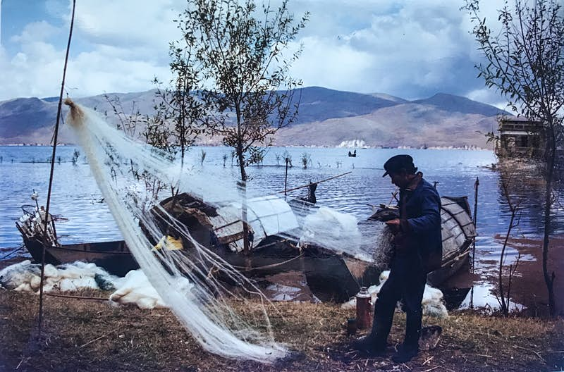 A fisherman detangles his nets on the banks of a river. He's wearing an overcoat and a black cap. The sky is blue and scattered with white clouds and the other bank of the river is in the background of the image. Hilly peaks frame the river. Two boats are moored on the bank next to the fisherman.