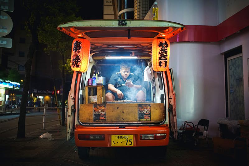 A yakitori vendor is sat in the back of his van behind his griddle while checking his phone in Okinawa, Japan; he is flanked by lanterns on each side hanging from the open hatch door.