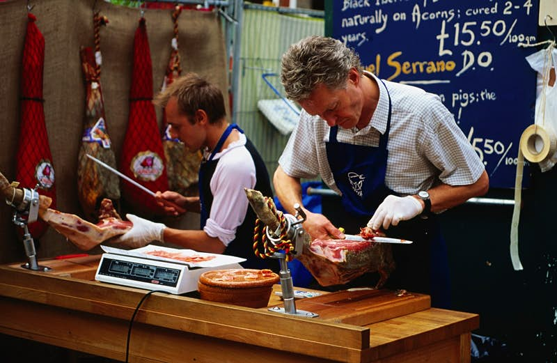 Two market workers in aprons carve jamón directly from the joint at a stall Borough Market