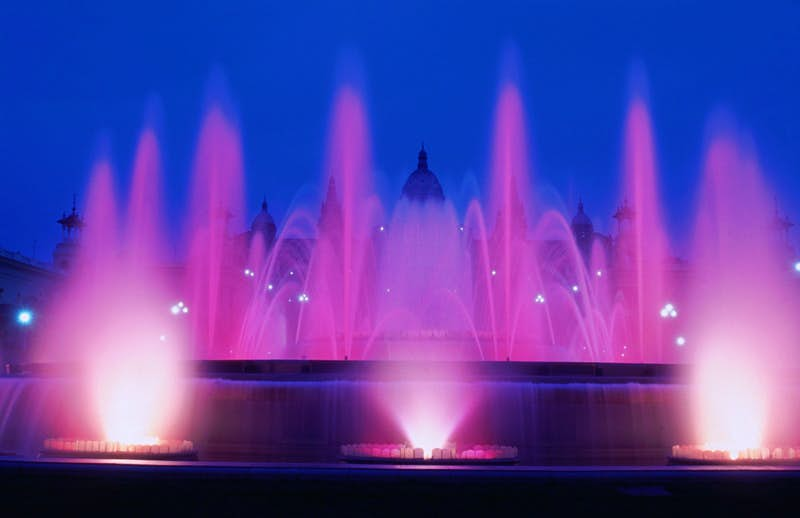 The fountain is lit up pink, with at least six jets of water shooting high into the sky, and many arcing over the fountain.