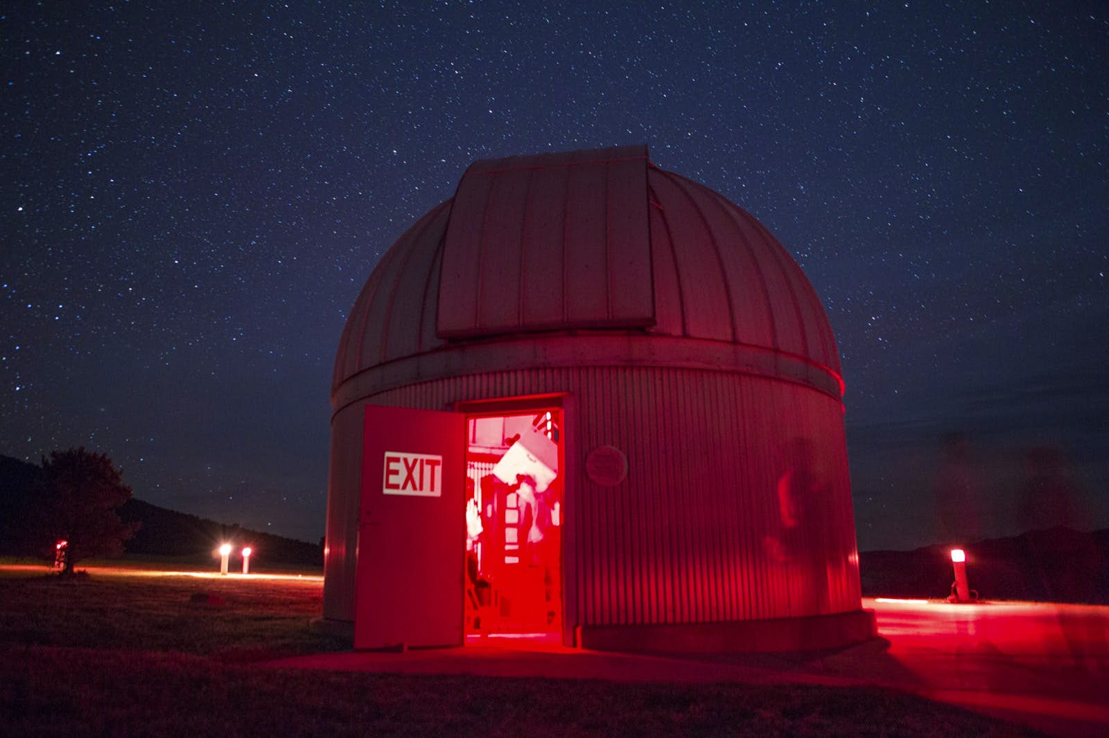 A domed telescope hub at night, lit by red light with the door open, revealing a large 'exit' sign and a blurry interior; Apollo anniversary experiences