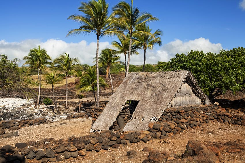 A series of large rocks form a rectangular perimeter around thatch house. There are rock walls and palm trees in the background; free things to do in Hawaii