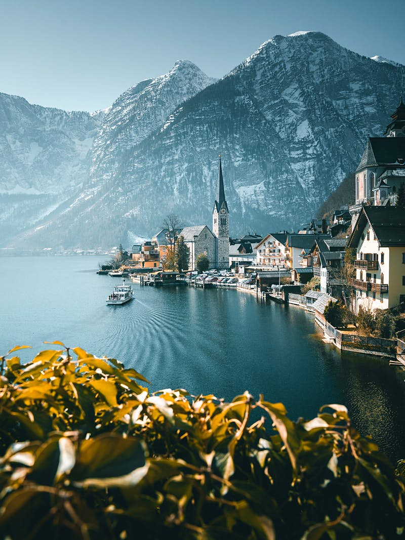 Hallstatt in Austria in winter; a picturesque town sits on the edge of a lake; there is a church with a spire and a boat sailing across the lake towards it. In the foreground is a yellow-tinged bush and in the background, dramatic snow-covered mountains.