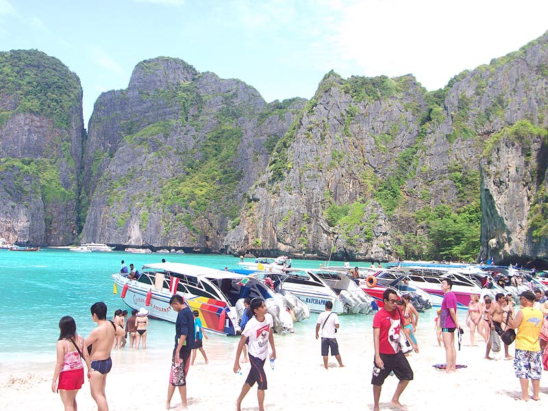 A beautiful cove is filled with speedboats and tourists in Thailand