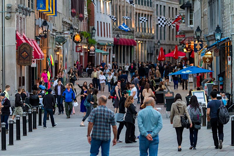 People walk along a cobblestoned street in Montreal with charming shops on both sides and plants, awnings and flags lending color to the gray stone walls; perfect weekend in Montreal