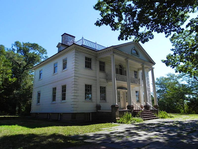 The exterior of the Morris-Jumel Mansion under a blue sky; historic homes