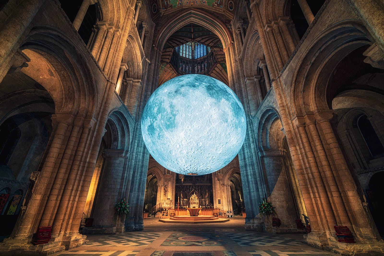 A huge glowing replica of the moon inside the softly lit vaults of a cathedral. The moon appears to be suspended in mid air, surrounded by grey stone columns and stained glass windows. The altar of the church is visible in the background.