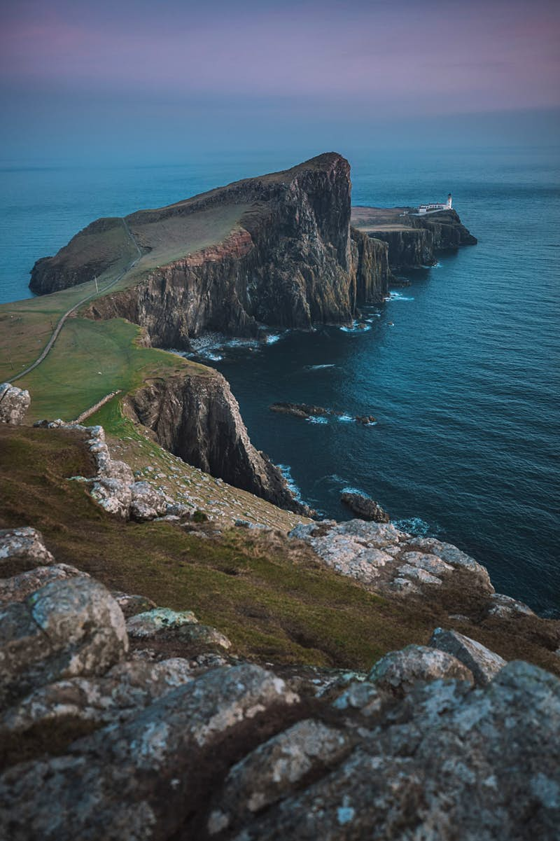 Looking out to Neist Point Lighthouse on the Isle of Skye, Scotland in the evening; it sits at the end of a long promontory of high rocky cliffs topped by grass.
