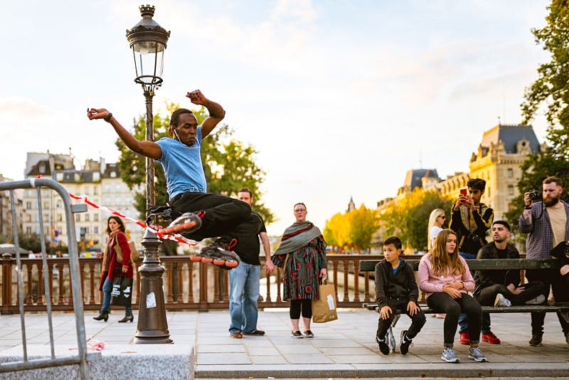 A rollerblader jumps some tape on a bridge over a river in Paris; there is an intricate lamppost behind him, and crowds milling around a bench watching; in the background are trees and a handsome building.