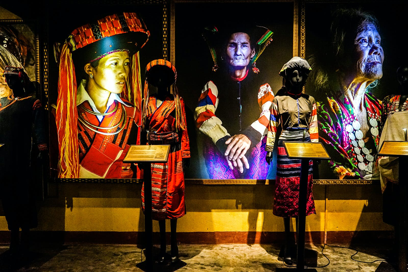 Two mannequins wearing traditional clothing stand in front of three large portraits of women in similar traditional clothing