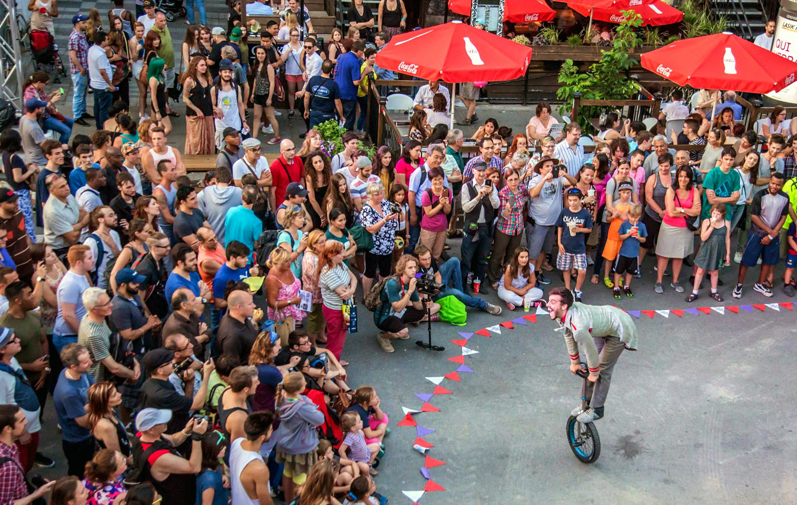 An acrobat stands on a unicycle in a funny pose as a crowd of spectators surround him, sitting on the ground