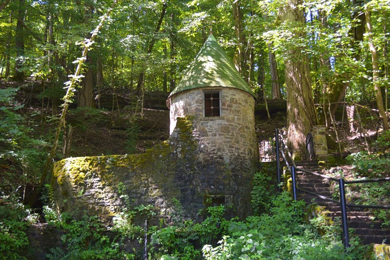 A stone wall and small turret covered in moss sits in the middle of a forest
