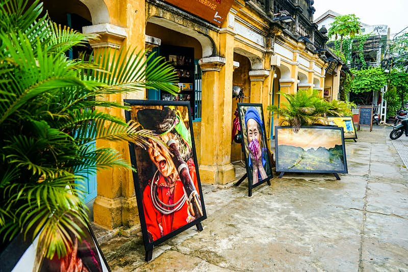 Large paintings of women in traditional dress sit either side of a yellow archway leading to a shop entrance