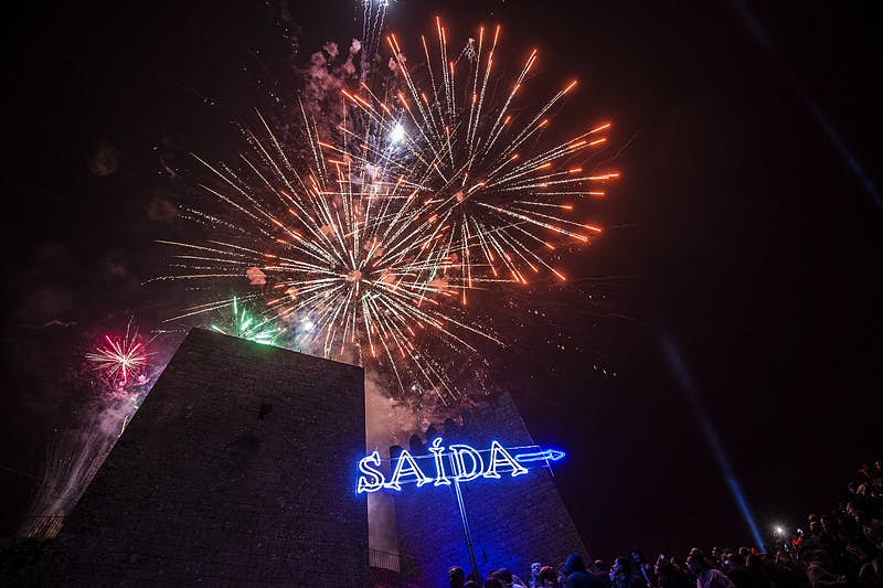 """Fireworks lighting up the sky at the Sexta13 festival, above a neon """"Saida"""" sign."""