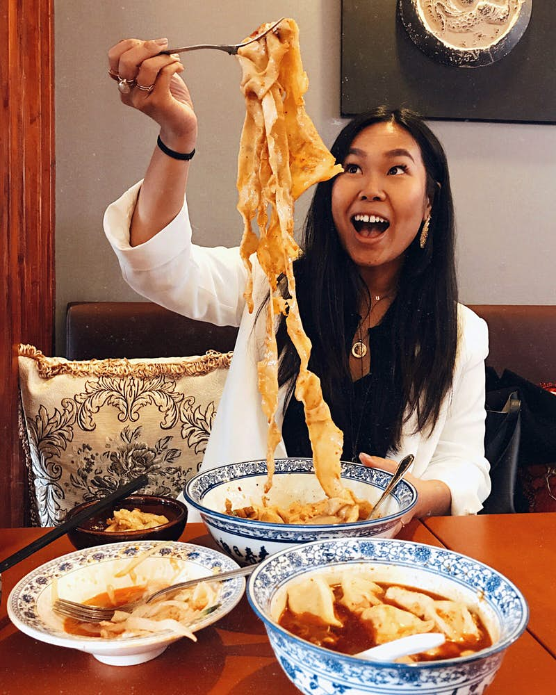 Shu Shi Lin raising pork biang biang noodles into the air from a bowl using a fork. Shu is looking up at the noodles in delight, there are two other saucy dishes on the table in white bowls with a blue pattern.